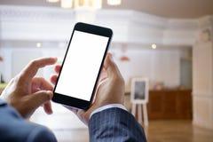 Podróżnik używa smartphone przy odprawy informacją przed hotelowym recepcyjnym biurkiem zdjęcia stock