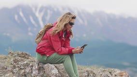 Podróżnik używa smartphone w górach podczas gdy relaksujący dziewczyna turysta trzyma telefon komórkowego zdjęcie wideo