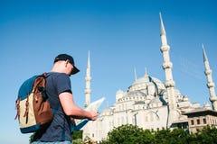 Podróżnik w baseball nakrętce z plecakiem jest przyglądający obok błękitnego meczetu mapa - sławny widok obraz stock