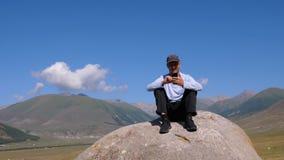 Podróżnik wyszukuje telefon podczas gdy siedzący na kamieniu z górami behind zbiory wideo