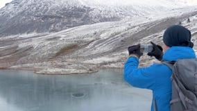 Podróżnik wzrasta wysoki punkt Patrzeje halnych szczyty pięknego jezioro i Fotografuje pięknego krajobraz zdjęcie wideo