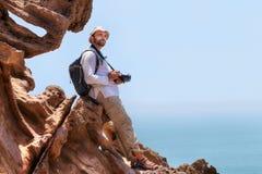 Podróżnik z kamerą siedzi na krawędzi falezy zdjęcia stock