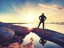 Podróżnik z plecaka stojakiem na skalistym brzeg i patrzeć wschód słońca Skalisty clif Zdjęcie Royalty Free