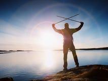 Podróżnik z plecaka stojakiem na skalistym brzeg i patrzeć wschód słońca Skalisty clif Fotografia Royalty Free
