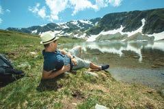 Podróżnika mężczyzna relaksuje blisko halnego jeziora zdjęcie stock