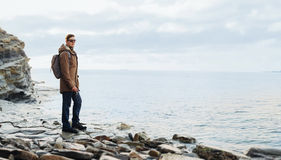 Podróżnika modnisia mężczyzna pozycja na linii brzegowej blisko morza Fotografia Stock
