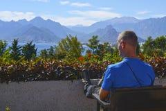 Podróżnika odpoczynkowy obsiadanie na ławce cieszy się pięknego widok Obrazy Royalty Free