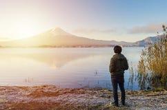 Podróżnika przyglądający wschód słońca Fuji i góra odbijamy na wodzie w Japan zdjęcia stock