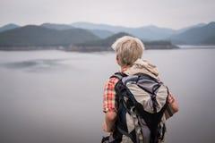 Podróżnika wycieczkowicza mężczyzna wycieczkuje blisko jeziora w wieczór z plecakiem Obraz Royalty Free