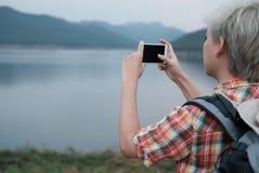 Podróżnika wycieczkowicza mężczyzna wycieczkuje blisko jeziora z plecakiem turystyczny backp Obrazy Royalty Free