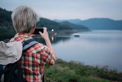 Podróżnika wycieczkowicza mężczyzna wycieczkuje blisko jeziora z plecakiem turystyczny backp Obraz Stock