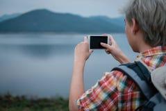 Podróżnika wycieczkowicza mężczyzna wycieczkuje blisko jeziora z plecakiem turystyczny backp Zdjęcia Royalty Free