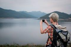 Podróżnika wycieczkowicza mężczyzna wycieczkuje blisko jeziora z plecakiem turystyczny backp Zdjęcie Stock