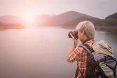 Podróżnika wycieczkowicza mężczyzna wycieczkuje blisko jeziora z plecakiem turystyczny backp Obrazy Stock