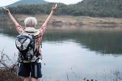 Podróżnika wycieczkowicza mężczyzna z plecak podwyżką wręcza blisko jeziora Turysta Fotografia Stock
