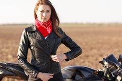 Podróżować na rowerze Poważny beeautiful chłodno motocyklista zapina czarną skórzaną kurtkę, czerwone bandany na szyi, cieszy się zdjęcie royalty free