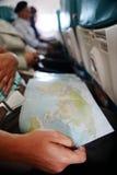 Podróżujący i patrzejący przy mapę wśrodku samolotu Obrazy Royalty Free