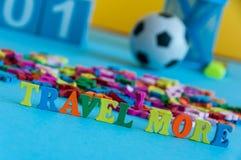 Podróżuje Bardziej - słowo komponującego mali barwioni listy na biznesowym miejscu pracy agent biura podróży lub biznesmen Lato Zdjęcie Stock