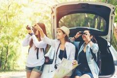 Podróżuje grupowego azjatykciego kobieta podróżnika obsiadanie na hatchback samochodzie dla wycieczki drogi z outdoors lasem w wa zdjęcie stock