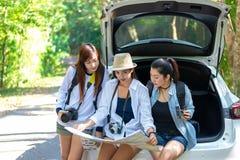 Podróżuje grupowego azjatykciego kobieta podróżnika obsiadanie na hatchback samochodzie dla wycieczki drogi z outdoors lasem w wa zdjęcia stock