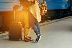Podróżuje pary młodzi kochankowie całuje outdoors z zbliżeniem na nogach i butach Dworzec na tle Ciepły wieczór Zdjęcie Royalty Free