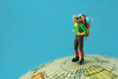 Podróżuje pojęcie gdy miniaturowy postać młody człowiek z plecaka sta Zdjęcia Stock