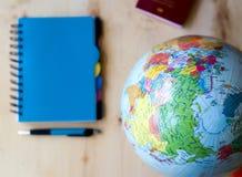 Podróżuje rzeczy, błękitny notepad, pióro, kula ziemska na drewnianym tle Obraz Royalty Free