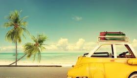Podróży miejsce przeznaczenia: rocznika klasyczny samochód parkujący blisko plaży z torbami na dachu fotografia royalty free