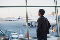 Podróży pojęcie z młodym człowiekiem w lotniskowym wnętrzu z miasto widokiem obok i płaskim lataniem Zdjęcie Stock