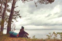 Podróżna osamotniona kobieta siedzi blisko lasowego jeziora i patrzeje daleki Obrazy Royalty Free
