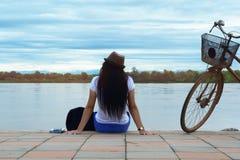 Podróżnik dziewczyna z torby i bicyklu obsiadaniem na cement ziemi Zdjęcie Royalty Free
