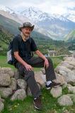 Podróżnik siedzi na skale przy odpoczynkiem w górach fotografia royalty free