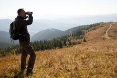 Podróżnik w gór spojrzeniach w lornetkach zdjęcia stock
