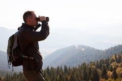 Podróżnik w gór spojrzeniach w lornetkach obrazy stock