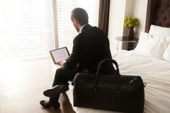 Podróżny biznesmen pracuje na laptopie od pokoju hotelowego daleko Zdjęcia Royalty Free