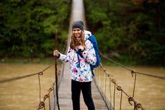 Podr??nicza kobieta z plecaka odprowadzeniem w lasowym skrzy?owaniu rzeki fotografia royalty free