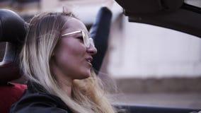 Podr??owa? kabrioletem Modnej blondynki uśmiechnięta kobieta w okularach przeciwsłonecznych i długim czarnym manicurze eleganckic zdjęcie wideo