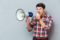 Podrażniony gniewny młody człowiek krzyczy z głośnikiem w szkockiej kraty koszula Zdjęcia Stock