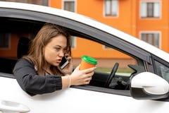 Podrażniony kobiety obsiadanie w miejsce pasażera i emocjonalnie opowiadać na telefonie zdjęcia stock