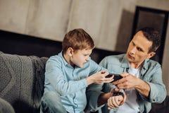 Podrażniony ojciec i syn walczy nad telefonem zdjęcia royalty free