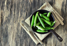 Pods of fresh green peas. In a vintage pan on the old wooden table. Rustic style. Organic vegetables. Selective focus. Tinted image. View from above royalty free stock photo