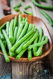 Pods of fresh organic green beans in a wooden bowl closeup. On a rustic table Stock Photo