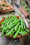 Pods of fresh organic green beans in a wooden bowl closeup. On a rustic table Royalty Free Stock Image