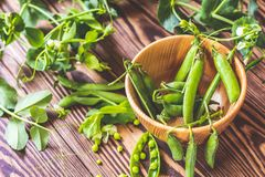 Pods of green peas and pea on dark wooden surface royalty free stock photos