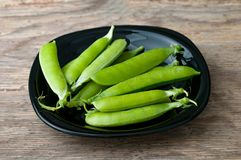 Pods of green peas in plate on wooden background. The Pods of green peas in plate on wooden background Stock Images