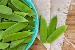 Pods of green peas on a wooden background Royalty Free Stock Images