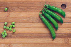 Pods of green peas on a wooden chopping Board top view. Space for text. Royalty Free Stock Photos