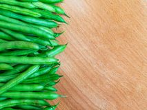 Pods of green raw beans top view on wooden surface, text space stock photo