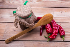 Pods hot pepper, a wooden spoon and a jar of sauce Royalty Free Stock Image