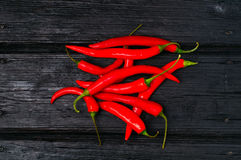 Pods of red hot chili peppers on old black wooden background Stock Photos